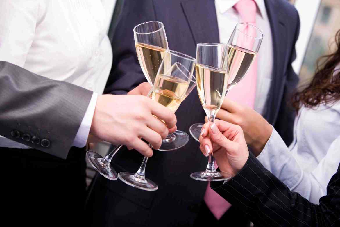 A group of business people clinking filled champagne flutes.