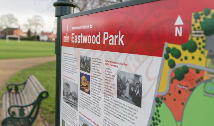A sign and a bench at Eastwood Park where Hasland Village Hall is located.