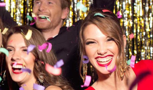 A group of twenty-something people laughing as they thrown party confetti.