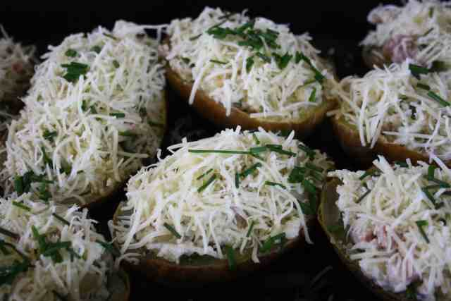 Twice Baked Stuffed Potatoes. Baked potato mixed with onions, bacon, cheese, garlic, chives and creme fraiche stuffed in potato skins and baked.