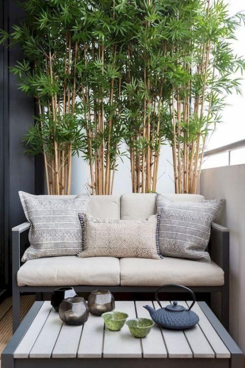 canapé et table basse sur balcon sans vis a vis avec bambou - Des astuces pour cacher le vis-à-vis sur le balcon sans se ruiner