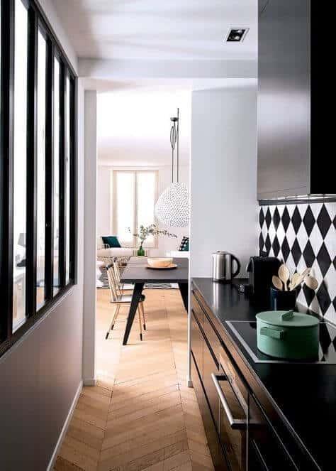 une cuisine étroite avec des meubles noirs et une verrière  - Aménager une cuisine dans une pièce étroite