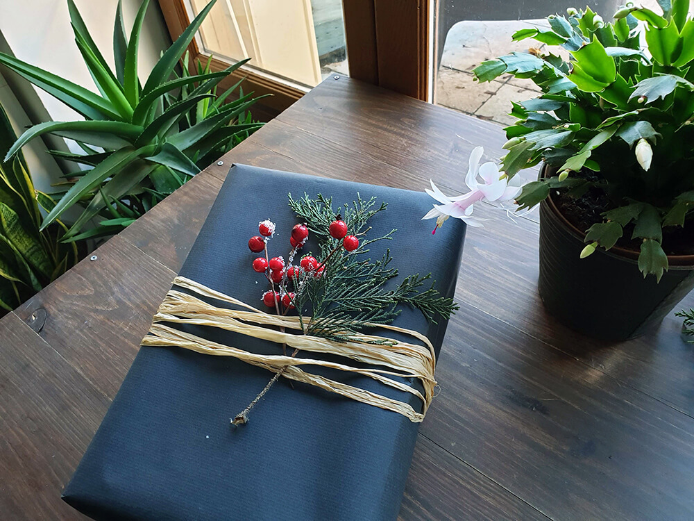 cadeau décoré avec du papier kraft du rafia et des feuillages - 7 idées d'emballage cadeau zéro déchet faciles à reproduire