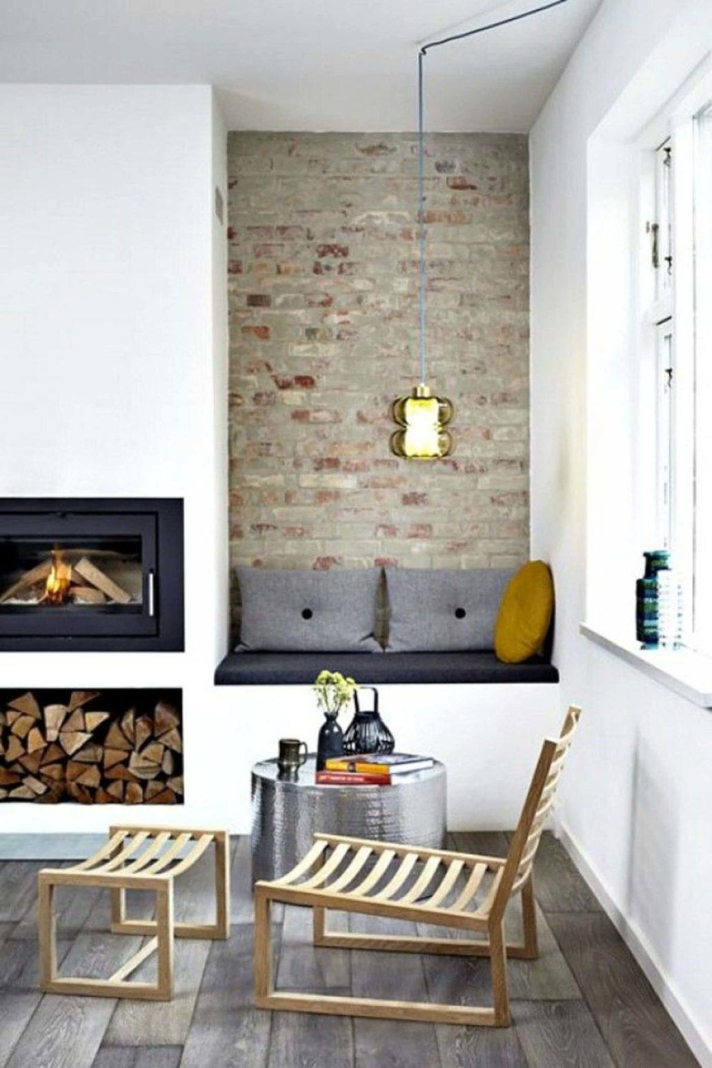 salon avec cheminée coin lecture et mur en pierre  1365x2048 - Comment décorer le mur du salon ?