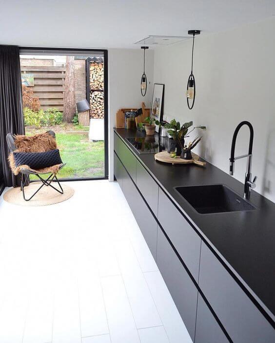 cuisine noire deco design avec fauteuil devant baie vitree - L'irrésistible cuisine noire : une inspiration moderne et tendance