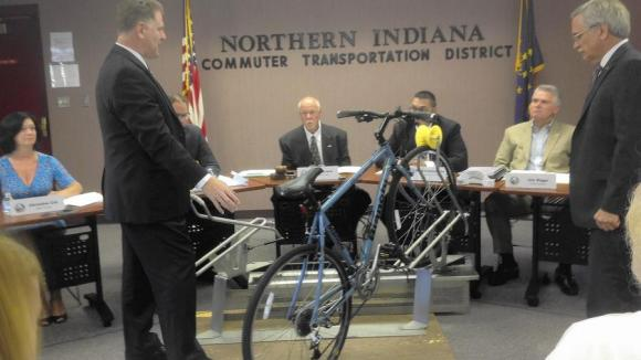 Mike Noland, general manager for the South Shore Line commuter rail, demonstrates a bike rack from SportWorks, the same company that makes bike racks for CTA and Pace buses. Photo: Carole Carlson