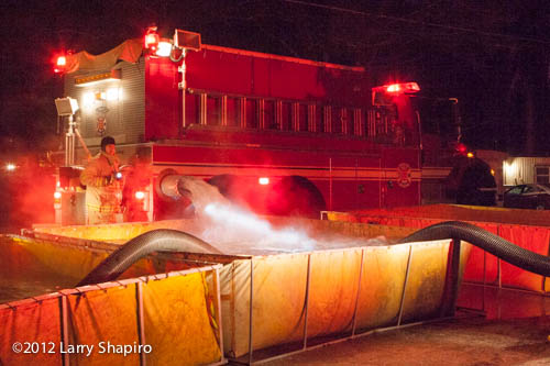 fire tanker dumping water into portable tank