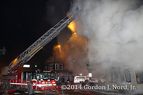 firemen use E-ONE tower ladder to battle commercial fire at night