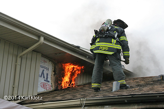 fireman on roof with flames