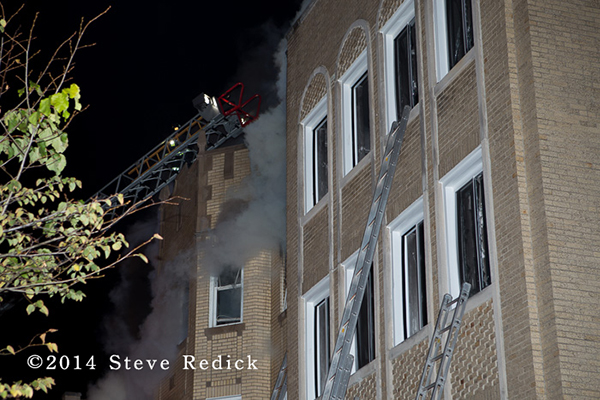 Chicago firefighters on aerial ladder with smoke