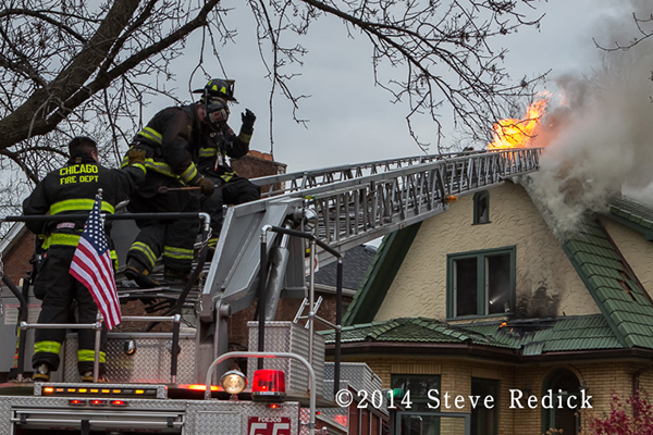 firemen on ladder with flames through roof