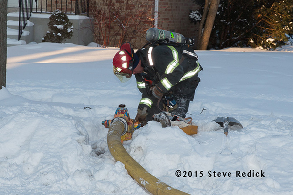 fireman at hydrant buried by snow