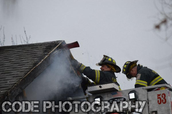 firemen overhaul roof of a house after a fire