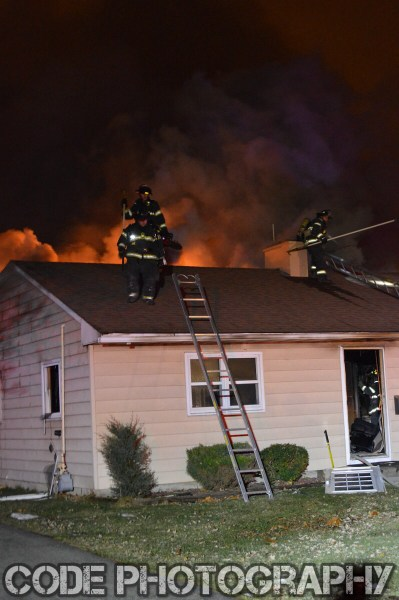firemen on roof of house fire at night