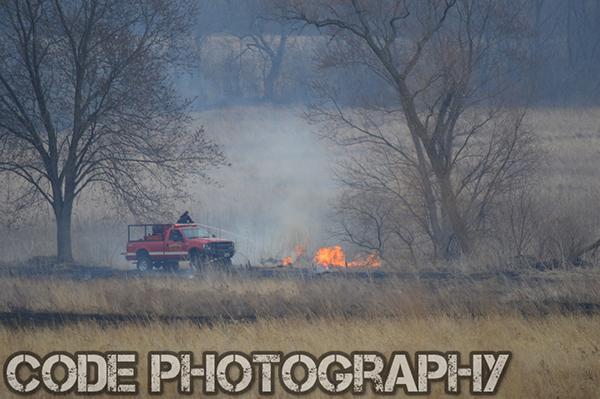 firemen extinguish a grass fire in a field