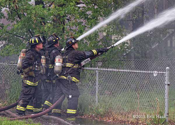 firemen with hose lines on chainlink fence