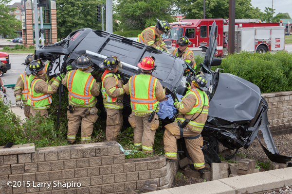 firemen remove the roof of a car