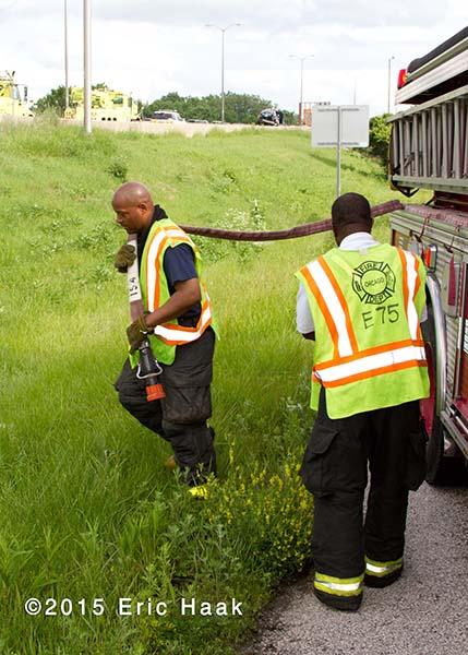 fireman pulls hose line wearing safety vest