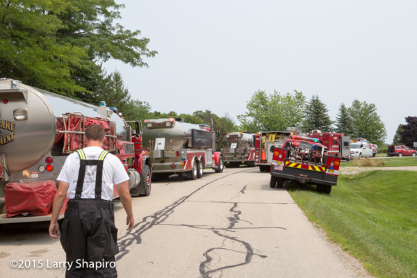 fire department water tenders staged at fire scene