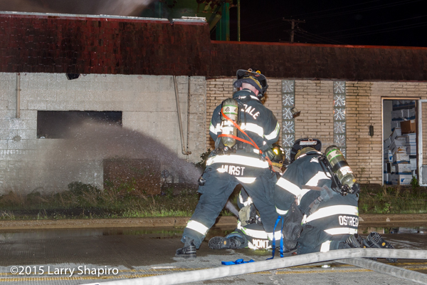 firemen with big hose line at night fire scene
