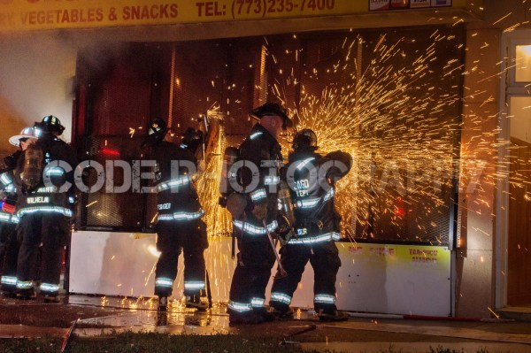 firefighters cut steel gates with saw at night