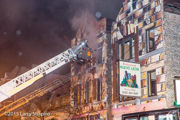 firemen in tower ladder battle fire