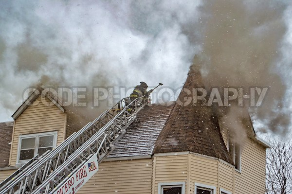firemen vent roof at fire with heavy smoke