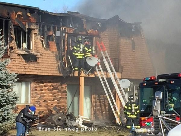 firemen overhaul apartment after fire