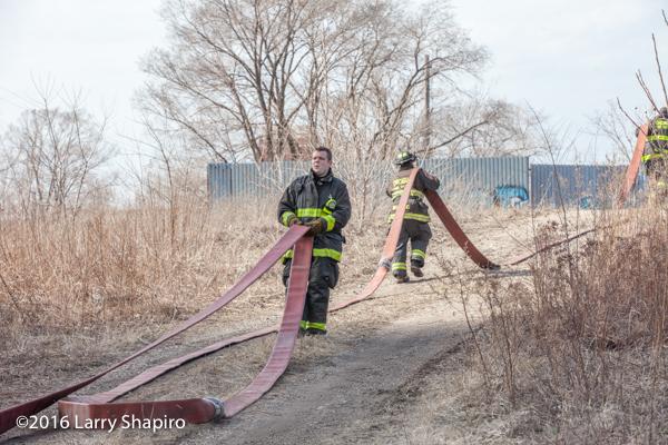 Firemen drag hose at fire scene