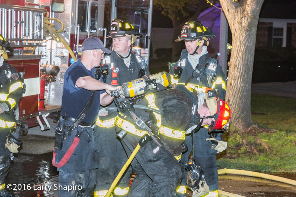 firefighters change air bottle at scene