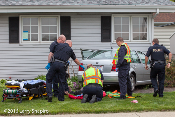 firefighters attend to accident victim on the ground
