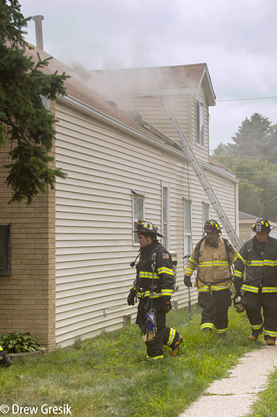firefighters survey house fire scene