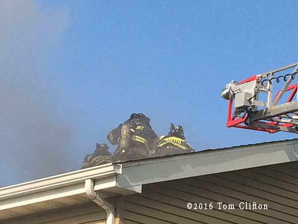 firefighters on roof at house fire