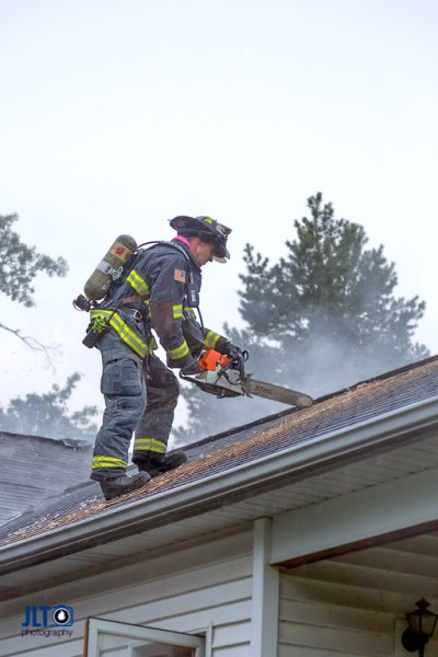 firefighter on roof ventilating house during a fire with a saw