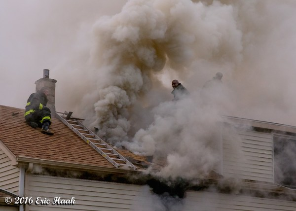 Firefighters engulfed in smoke on house roof
