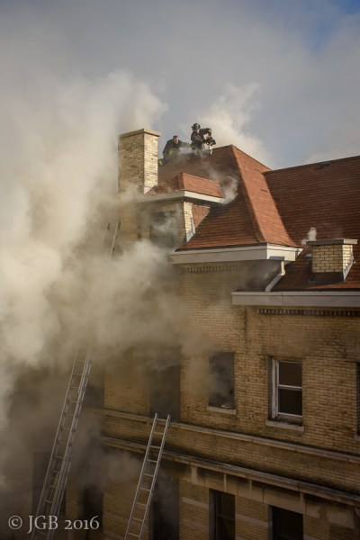 firefighters venting a roof as smoke billows from large home