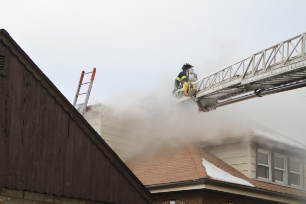Firefighter on aerial ladder with smoke