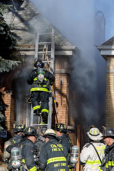 firefighter climbs ground ladder at house fire