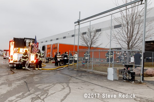 firefighters standby at warehouse fire