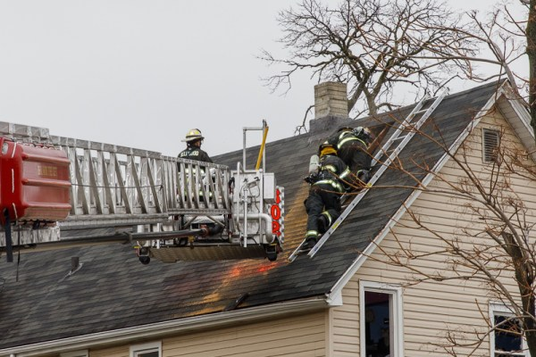 firefighters overhaul roof after house fire