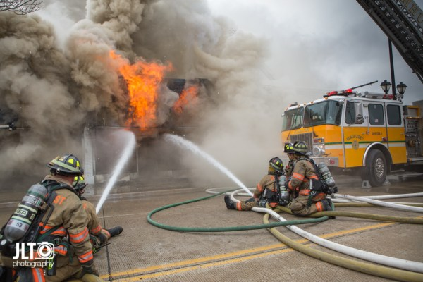 firefighters in street battle fire with which smoke and flames
