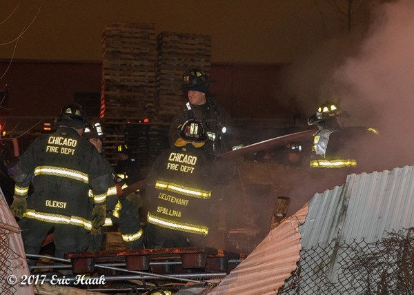 firefighters in junk yard at night