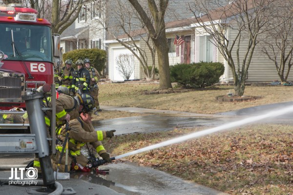 firefighters spray water on house fire