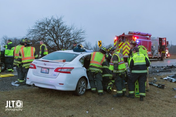 firefighters work to free occupants trapped in a car