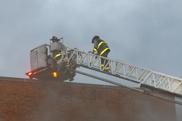 Firefighters ascend tower ladder to the roof