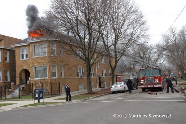 flames from attic at building fire