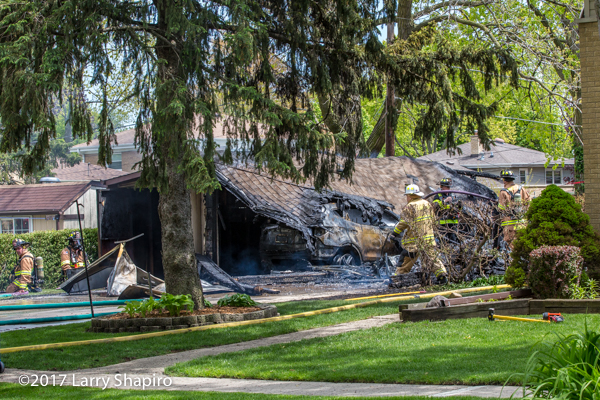 Firefighters at the scene of a detached garage that was destroyed by fire