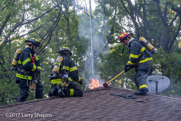 Firefighters vent roof of a house