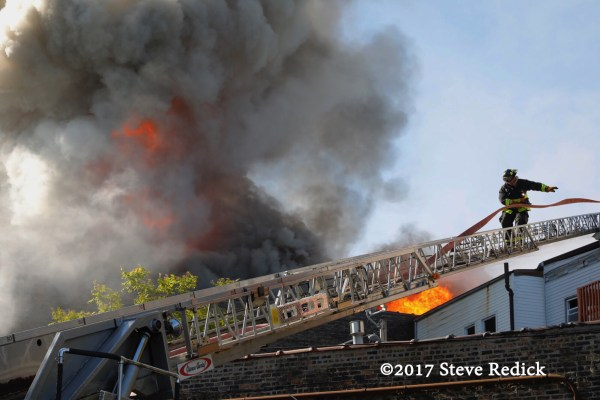 firefighter on aerial ladder with fire
