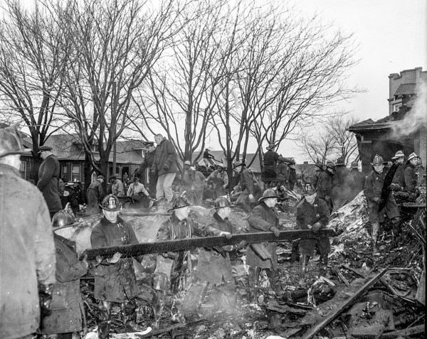 Firefighters work at an airplane crash site 11-24-59 in Chicago